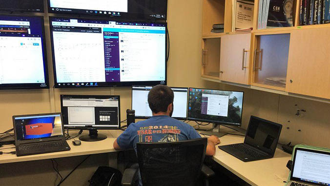 Student sitting in front of multiple computer screens