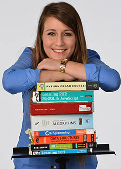 Svrcina leaning atop a stack of books