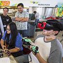 Students holding ukulele, one with a V R headset