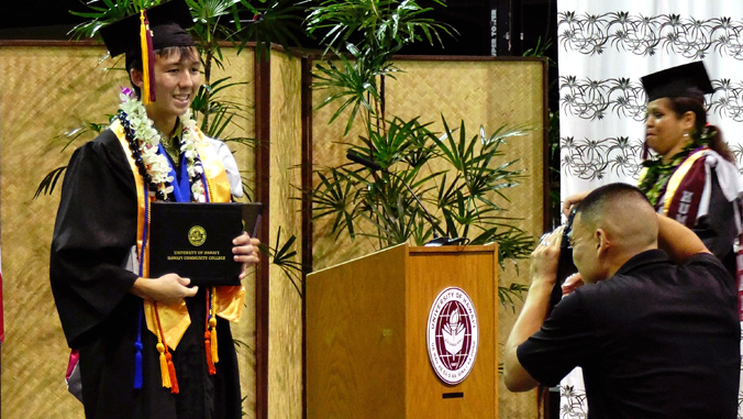 Okahara-Olsen taking a photo holding his diploma