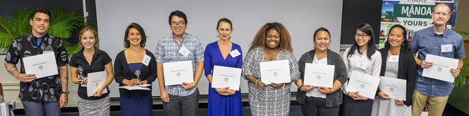 10 people standing in a line holding certificates