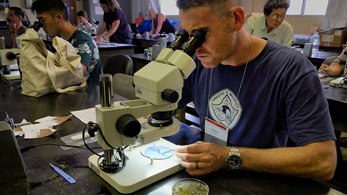 A man in a lab looking through a microscope