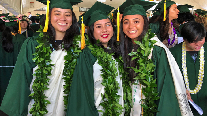 3 graduating student at commencement wearing their kihei