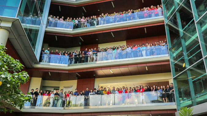 large group of people standing on multiple floors of UH Cancer Center walkways