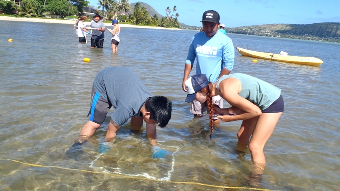 two students collecting algae samples in the ocean