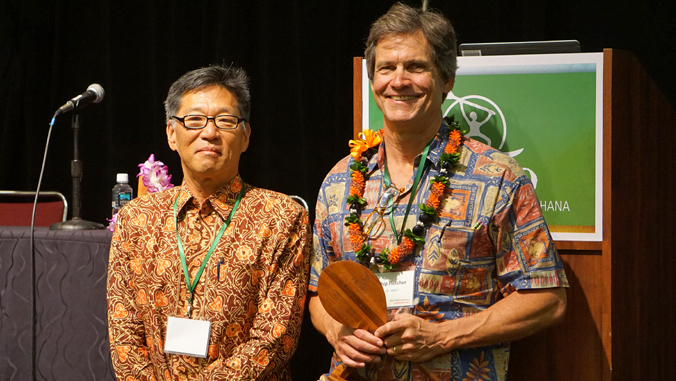 two people standing next to each other, one holding an award