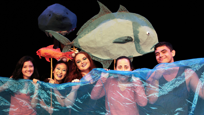 five people holding a plastic blue sheet with a fish behind them