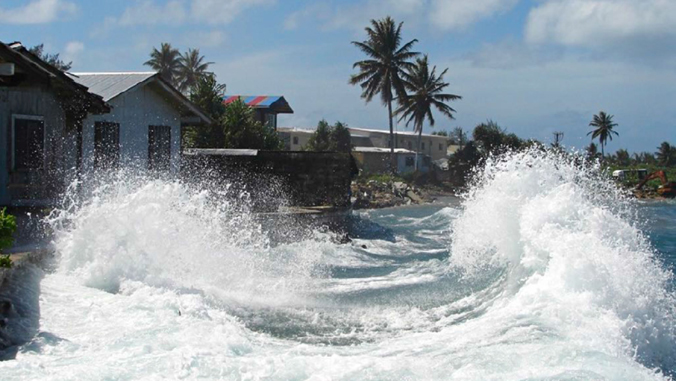 waves crashing against shoreline by houses