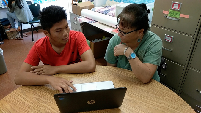Student with counselor looking at a laptop