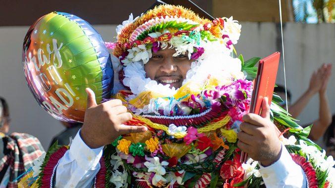 student in graduation cap and gown with lots of lei