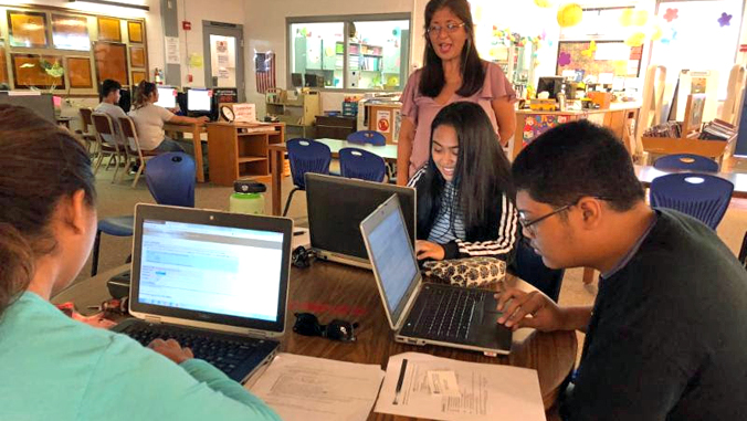 students looking at computer sitting a a table