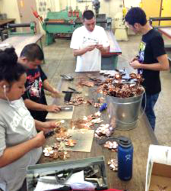 student putting together copper roses
