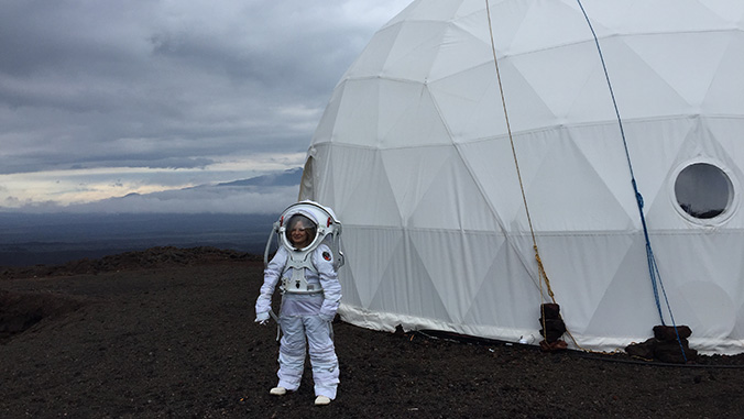 Researcher in space suit in front of HI SEAS dome