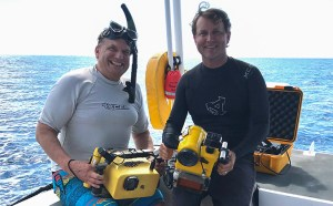 Two researchers on a boat with recording equipment