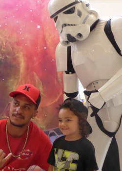 parent and child posing with stormtrooper