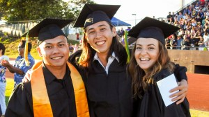 three students in graduation regalia