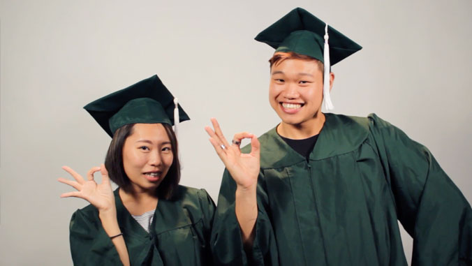 two uh manoa students in their graduation gowns