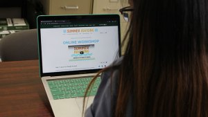 Back view of a student looking at the Summer Advising website on a laptop computer