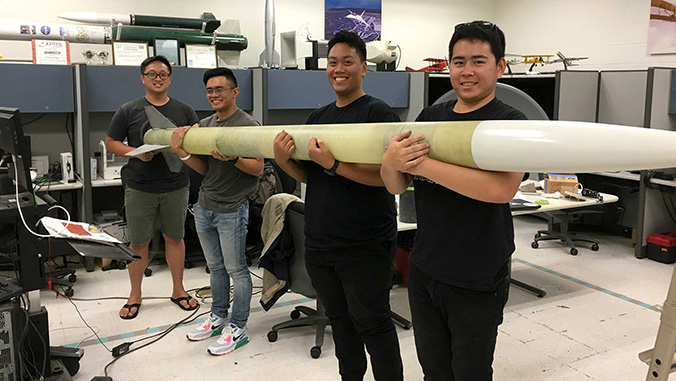 Four students holding a rocket