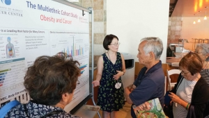woman pointing to presentation board surrounded by people