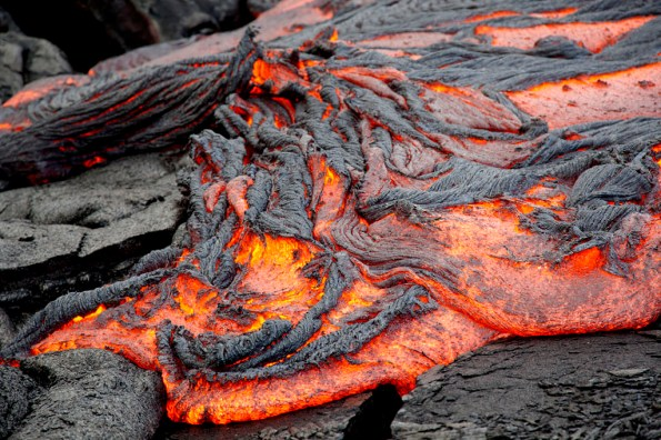 At the front of the lava surge, the thin surface crust rolls up as it advances in April, creating a ropey pahoehoe texture. USGS Photo by David Dow