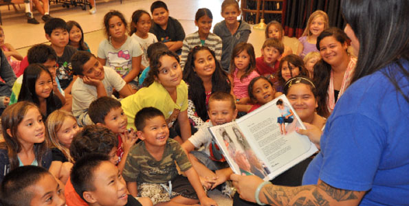 "Hakunani Anakalea, group leader at the A+ program at Holualoa Elementary School, reads ""Pearl Harbor Warriors: The Bugler, The Pilot, The Friendship.""  (Photo courtesy of Fern Gavelek Communications)"