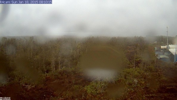 A photo looking west from a research camera temporarily positioned southeast of the Pāhoa Marketplace, this image shows the June 27th lava flow advancing from left to right. The image was taken at 8:10 a.m. Sunday, January 18, 2015. This camera that took this was installed through a collaboration between the USGS Hawaiian Volcano Observatory, Oceanic Time Warner Cable, and Bryson's Cinders Inc.