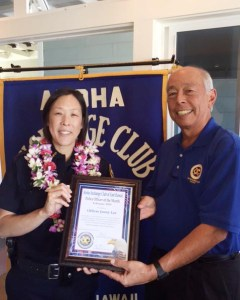 Aloha Exchange board member Joey Estrella presents an 'Officer of the Month' award to Officer Jenny Lee.