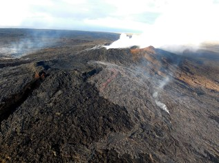 The two new flows that broke out on the flanks of the Puʻu ʻŌʻō cone on Kīlauea Volcano's East Rift Zone on May 24 remained active early the morning of Friday, May 27, 2016. The flows were spreading laterally near the vent, but making little forward progress; as a result, they were not posing a threat to any community. The silvery sheen of new lava erupting from the northern breakout (center) and eastern breakout (far left) stands out in contrast to the older flows on and around Puʻu ʻŌʻō. Photo taken Friday, May 27, 2016 courtesy of USGS/HVO