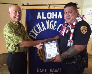 Aloha Exchange Club member Joey Estrella presents an 'Officer of the Month' award to Officer Jared Cabatu.