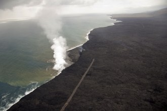 Lava continues to enter the ocean at Kamokuna, where a lava delta about 19 acres in size has been built. The gravel emergency access road is visible on both sides of the surface flow that cut it. The view is to the southwest. Photo taken Tuesday, November 29, 2016 courtesy of USGS/HVO