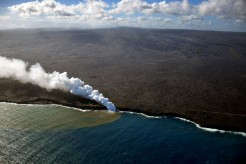 The episode 61g flow continues to enter the ocean at the Kamokuna ocean entry (center), and was producing a robust plume. The western Kamokuna delta, which was abandoned in late September 2016, is visible to the left of the entry. A few weak surface breakouts were still active on the coastal plain, but most surface activity is within approximately 3.5 km (2.2 miles) of the vent. The episode 61g tube is marked by fume traces that can be seen along the flow field, and Puʻu ʻŌʻō is visible in the center of the skyline. Photo taken Thursday, March 30, 2017 courtesy of USGS/HVO