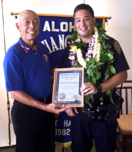 Aloha Exchange Club board member Joey Estrella presents an 'Officer of the Month' award to Officer Thomas Chun-Ming