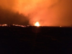 Overflows from the perched lava channel are seen as incandescent (glowing) fingers moving down the sides of the channel (left side of photo). Fissure 8 lava fountain in photo center. Photo taken Wednesday, June 27, 2018 courtesy of U.S. Geological Survey