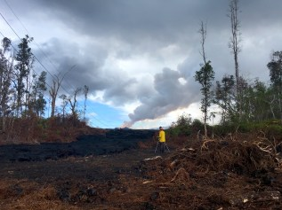 Hawaiian Volcano Observatory geologist Matt Patrick acquires video of fissure 8 and the lava channel from Pohoiki Road/Highway 132. The video is used to document fountain behavior and lava flow characteristics, and how they change with time. Photo taken Saturday, June 30, 2018 courtesy of U.S. Geological Survey