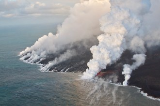 Having crusted over about 0.8 km (0.5 mi) upchannel from the ocean entry, lava oozes from the flow's molten interior to enter the sea along a broad flow front on the northern (Kapoho) side of the flow. Photo taken Thursday, July 5, 2018 courtesy of U.S. Geological Survey