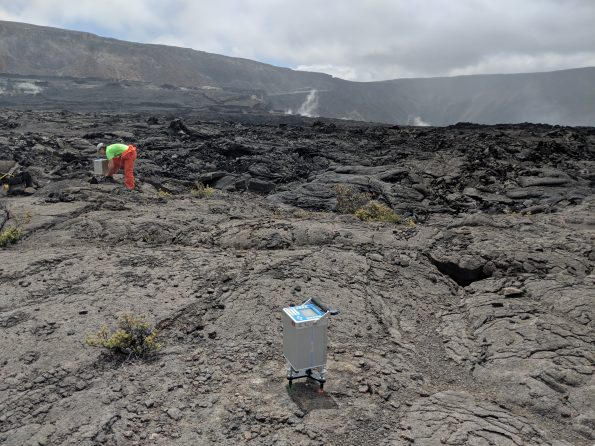 A scientist takes a gravity reading at a station located on the down-dropped block of Kīlauea caldera, which subsided as an intact structure, while a second gravity instrument (foreground) records data. Many of the preexisting gravity stations, which have been measured for years, survived Kīlauea's 2018 summit collapse. Remeasuring the stations now and comparing the data to previous results could provide information on what's happening below ground within the volcano's shallow magmatic system. USGS photo by M. Poland, 03/25/2019.