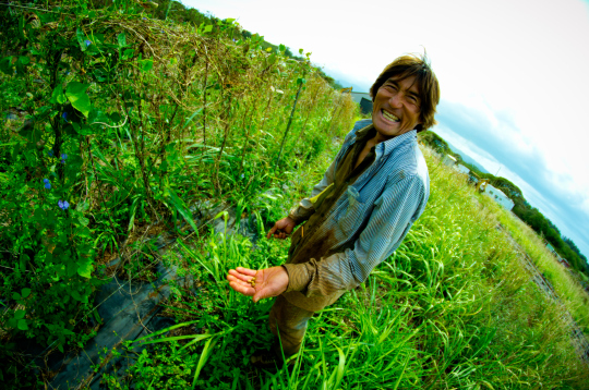 Oahu Organic Farms - Guy holding out hand with seeds & smiling