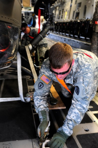 Specialist Benjamin Luckett, an OH-58D systems repairer assigned to Troop D, 2nd Squadron, 6th Cavalry Regiment, 25th Combat Aviation Brigade hooks up a ratchet strap tying down an OH-58D Kiowa Warrior in the back of an Air Force C-17 Globemaster III during a static load training session on Joint Base Pearl Harbor-Hickam, Hawaii, June 7.