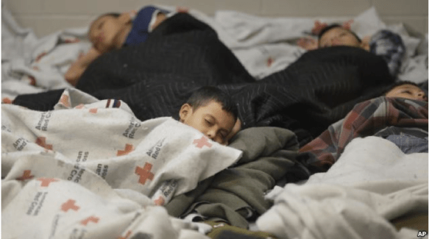 FILE - This June 18, 2014, file photo shows children detainees sleeping in a holding cell at a U.S. Customs and Border Protection processing facility in Brownsville,Texas.