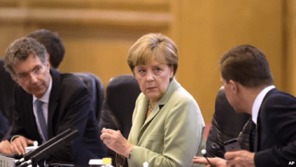 German Chancellor Angela Merkel (C) chats with her delegates as she attends a bilateral meeting with Chinese Premier Li Keqiang at the Great Hall of the People in Beijing, China, July 7, 2014.