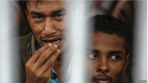 FILE - Rohingya people from Myanmar, who were rescued from human traffickers, react from inside a communal cell at Songkhla Immigration Detention Centre, near Thailand's border with Malaysia.