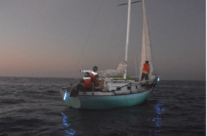 A mariner and his 25-foot sailing vessel are being towed to Molokai after spending 12 days lost at sea Dec. 9, 2014. Ron Ingraham is currently aboard Coast Guard Cutter Kiska, a 110-foot Island-class patrol boat home ported in Hilo, en route Kaunakakai, Molokai, with his sailing vessel Malia in tow. (U.S. Coast Guard courtesy photo)