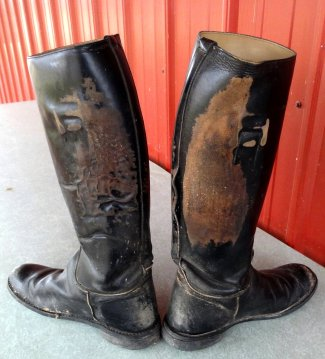 Worn leather patches on black riding boots