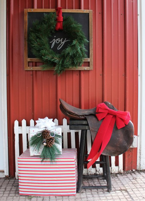 Cardboard boxes wrapped with ourdoor tablecloths decorated with evergreen and a hore bit make cute Christmas barn decorations!
