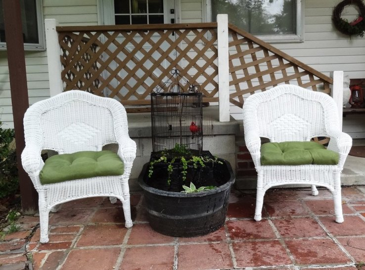 Wicker chairs and birdcage water feature on porch