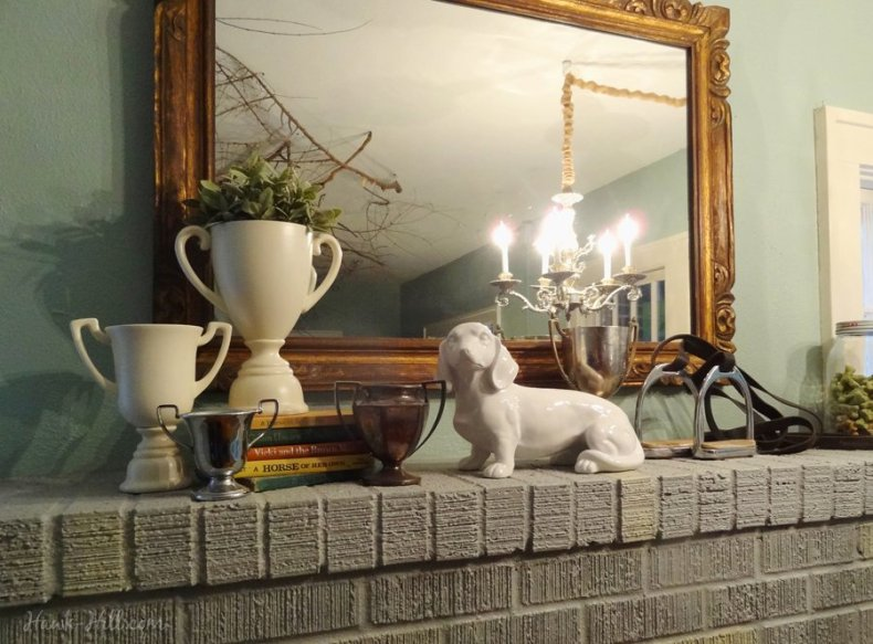 Equestrian fireplace mantle with trophy display, books, and stirrup irons.