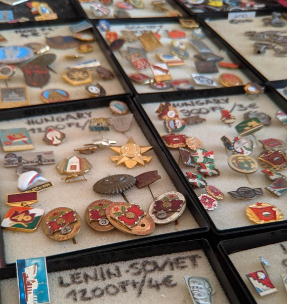 Cases full of decorative lapel pins for sale at a flea market in a ruin bar in Budapest Romania