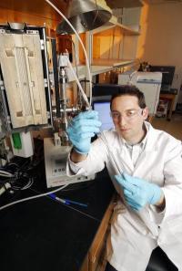 תלמיד מחקר בג'ורג'יה טק מראה את החומר המשמש ללכידת דו תחמוצת הפחמן מתחנות כוח