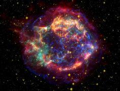 תמונה בצבע מדומה של קסיופיאה A, המשלבת מידע משלושה מקורות: אדום - מידע ממצפה החלל שפיצר, בכתום - מהאבל, ובירוק וכחול - מצ'נדרה